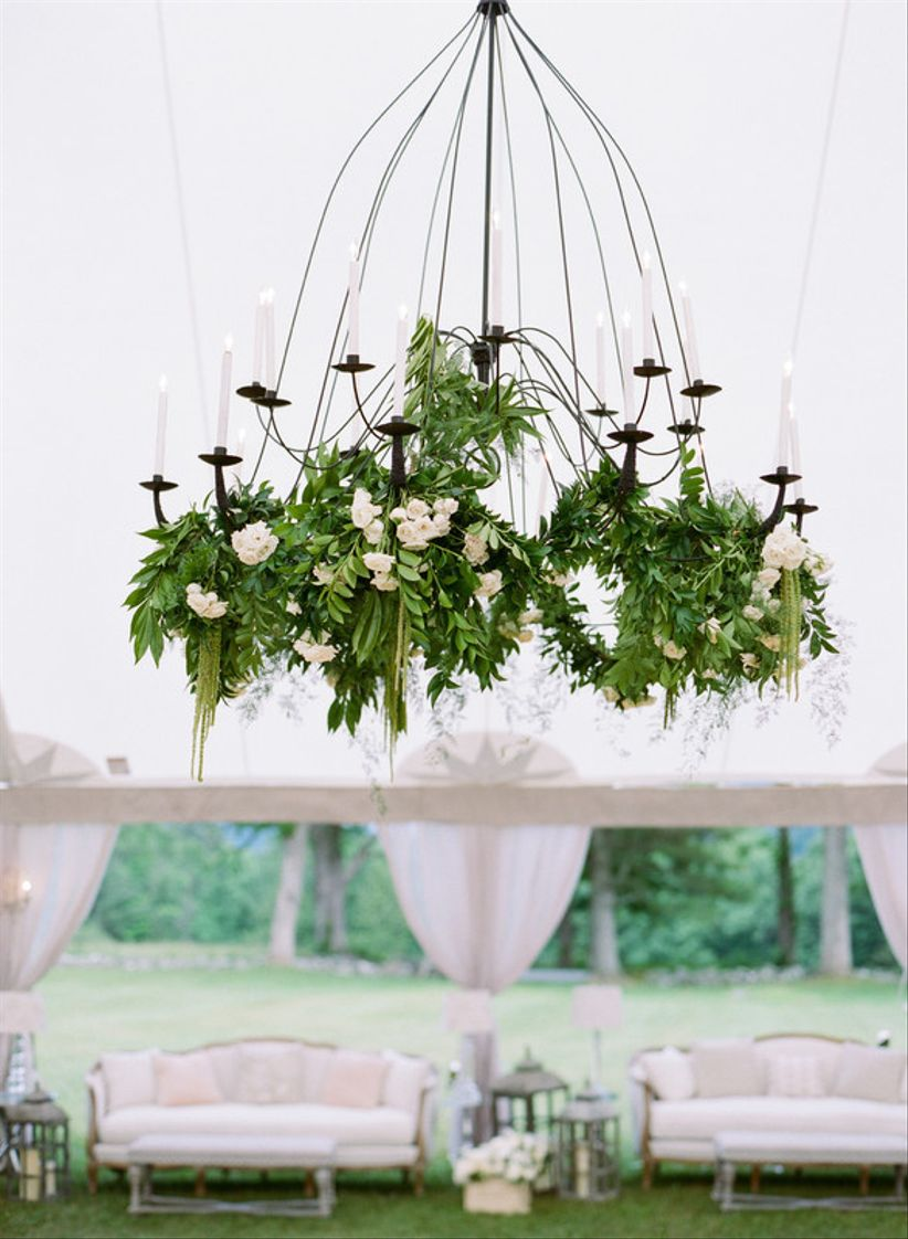iron chandelier is decorated with greenery and white flower garlands