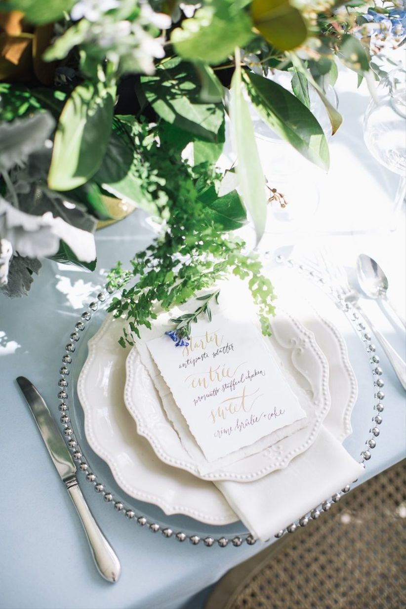 white and pale blue wedding place setting with greenery centerpiece