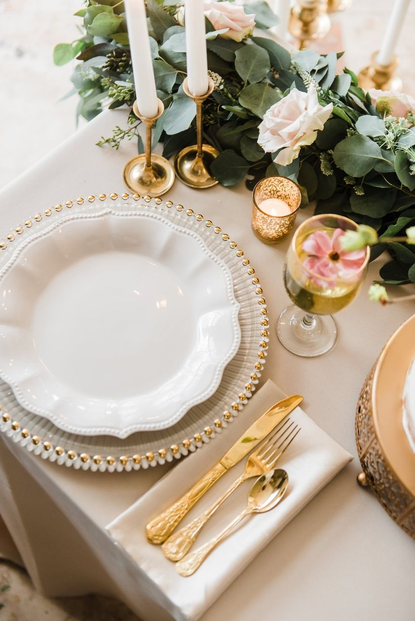 wedding place setting with ivory linens and gold flatware