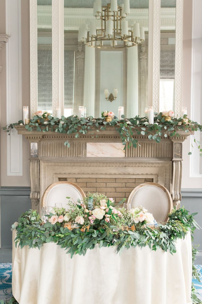 wedding sweetheart table with blush linens and greenery