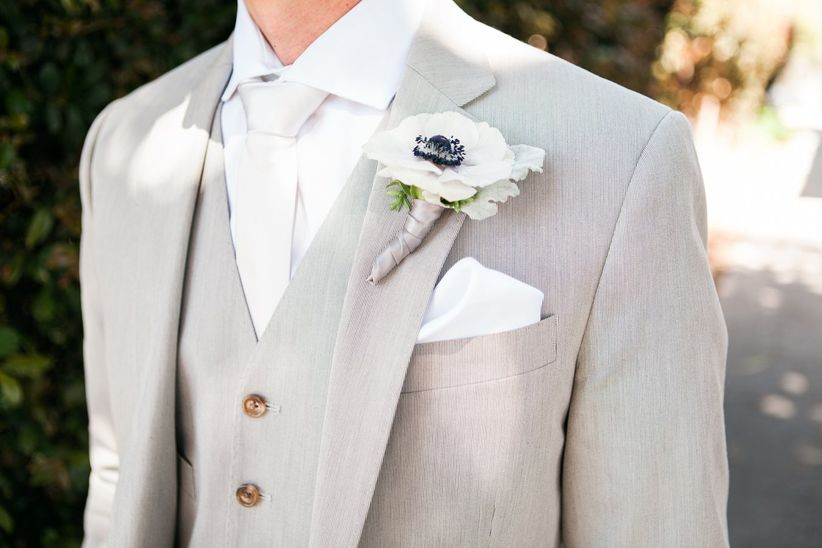 groom wearing light gray suit and white anemone boutonniere