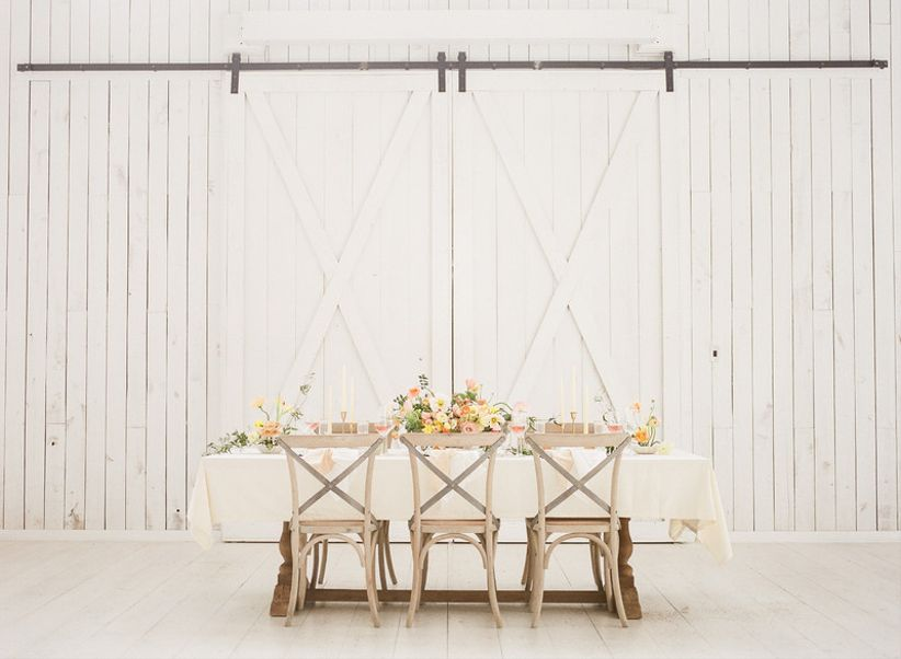 whitewashed X-back chairs at barn wedding reception