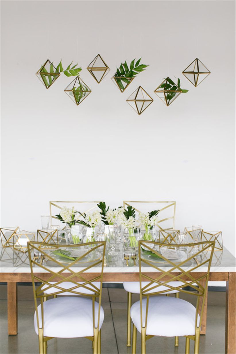 modern gold wedding chairs and greenery tablescape