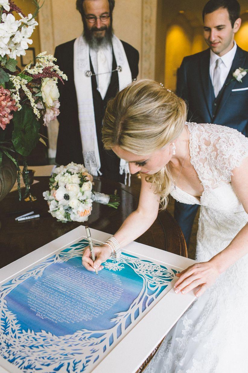 bride signing blue and white ketubah