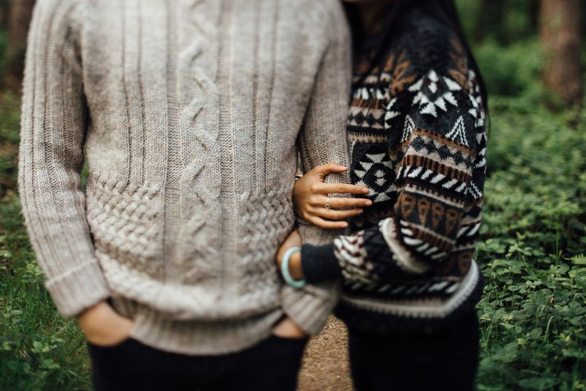 couple wearing cozy cable knit sweaters hug in a forest