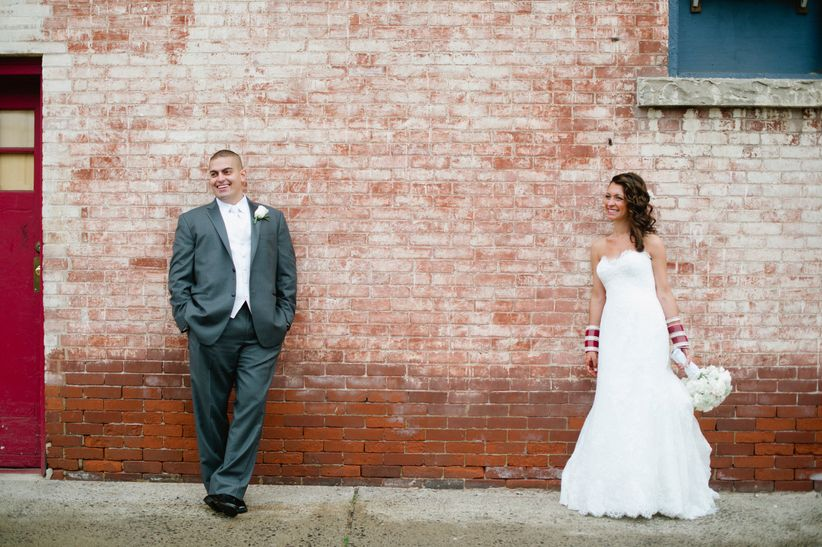 couple standing brick wall