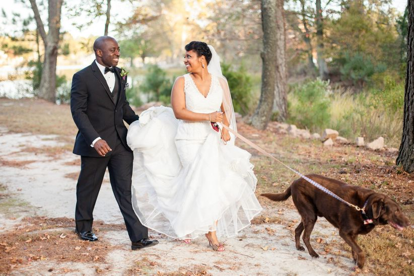 groom and bride walking dog