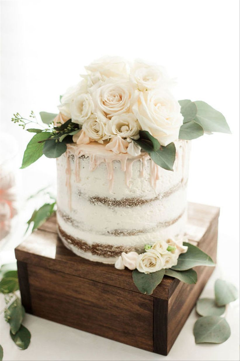 buttercream wedding cake with blush drip icing and roses