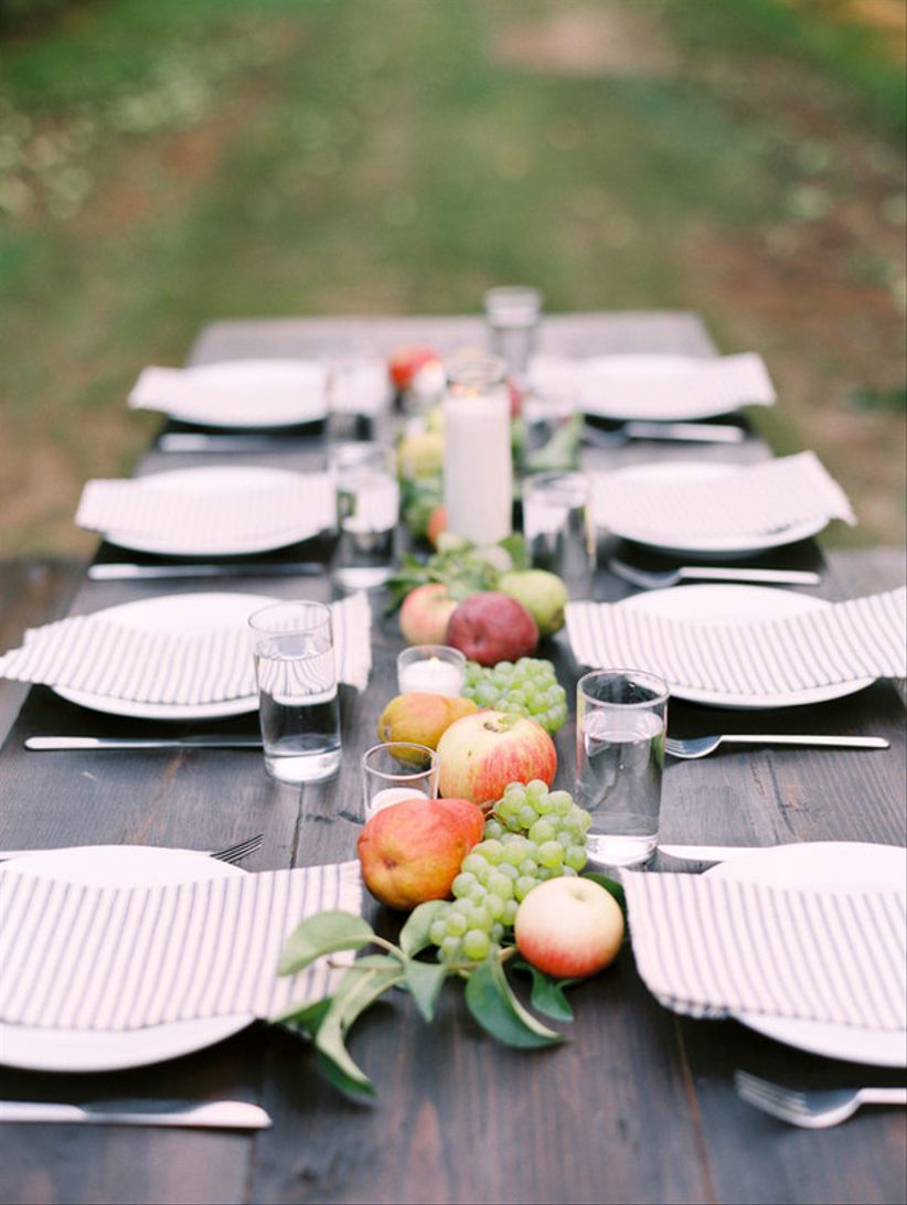 rustic wedding tablescape decorated with apples, grapes and gray stripe napkins