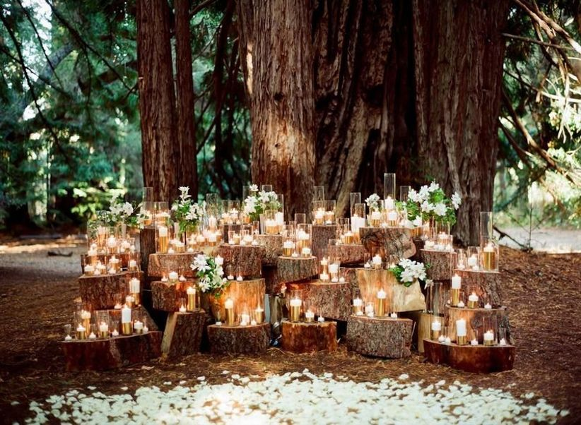 rustic wedding ceremony decor with candles and tree stumps