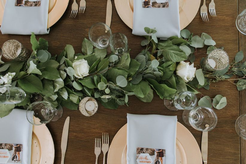 rustic wedding tablescape with greenery and gold charger plates