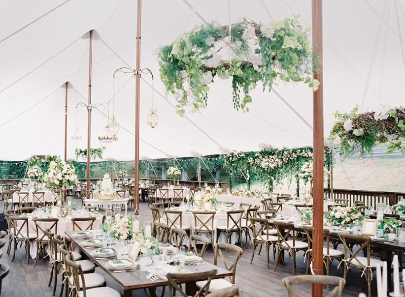 Sailcloth tent wedding reception with greenery chandeliers