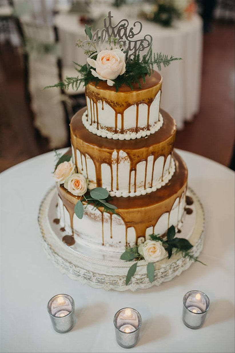 drip wedding cake decorated with caramel icing and flowers
