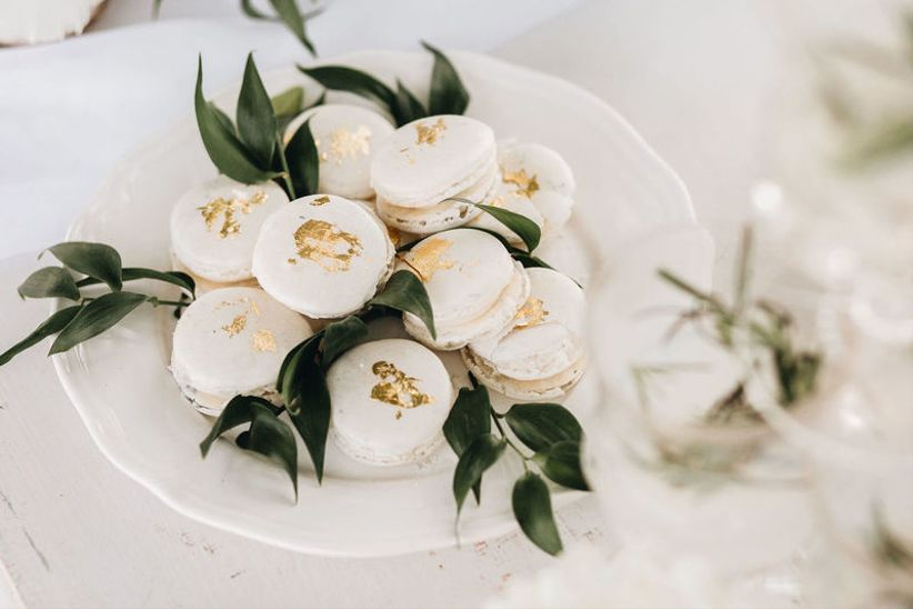 plate of white macarons with gold foil