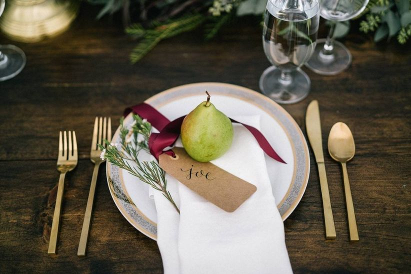 wedding reception place setting with fresh pear in the middle of the plate