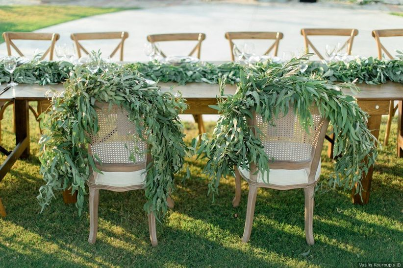 cane-back chairs at head table decorated with eucalyptus garlands