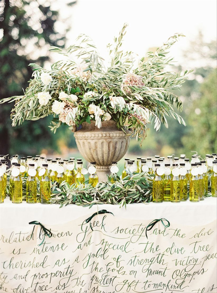 wedding favor display bottles of olive oil and greenery in stone urn