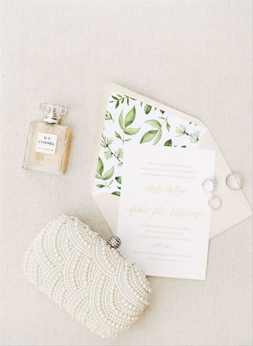 elegant wedding invitation suite flat lay with pearl beaded clutch