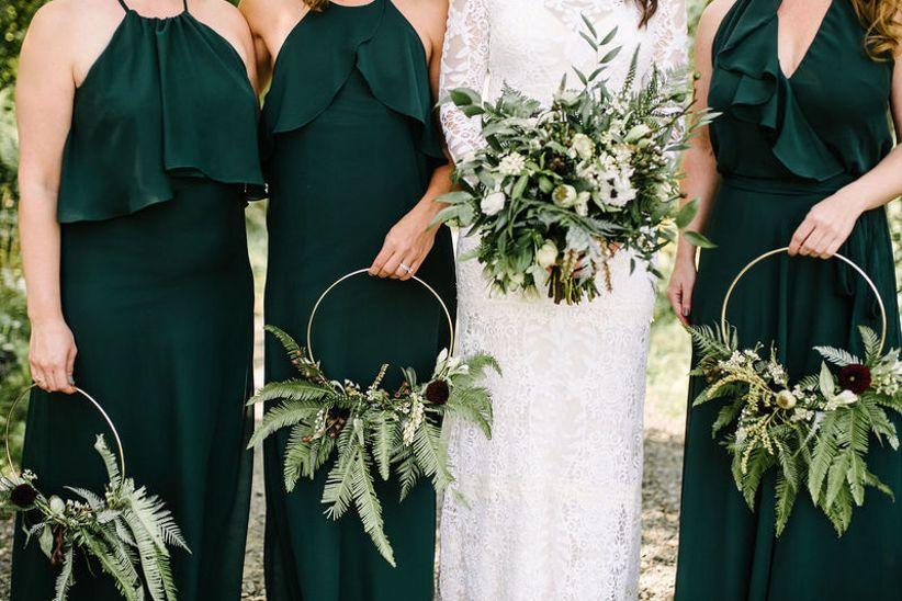 bridesmaids wearing emerald green dresses holding greenery wreaths