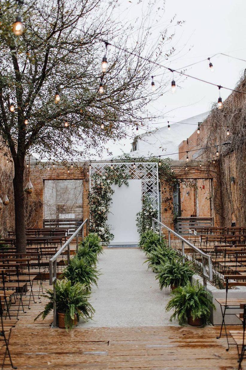 outdoor wedding ceremony aisle lined with ferns in pots