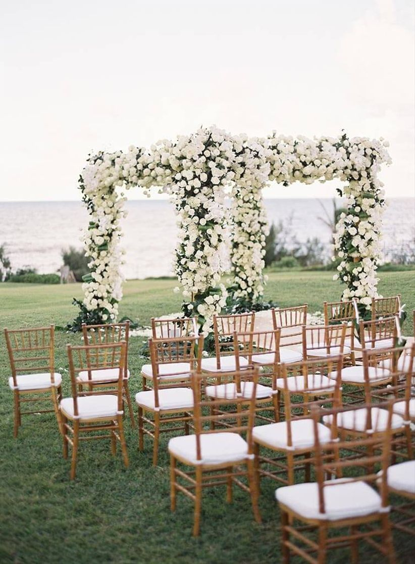 white rose-covered chuppah at oceanfront hawaii wedding venue