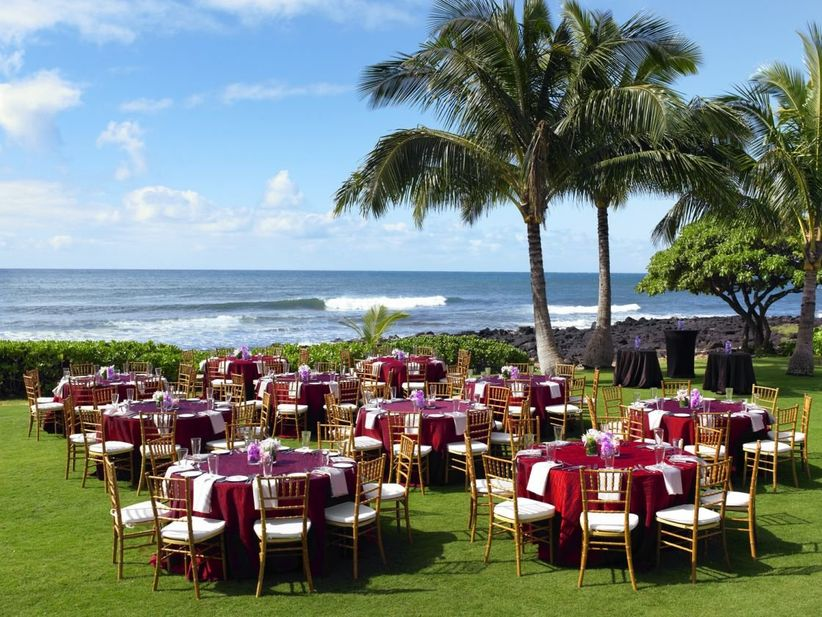 outdoor kauai wedding reception round tables set up on grass with ocean in the background