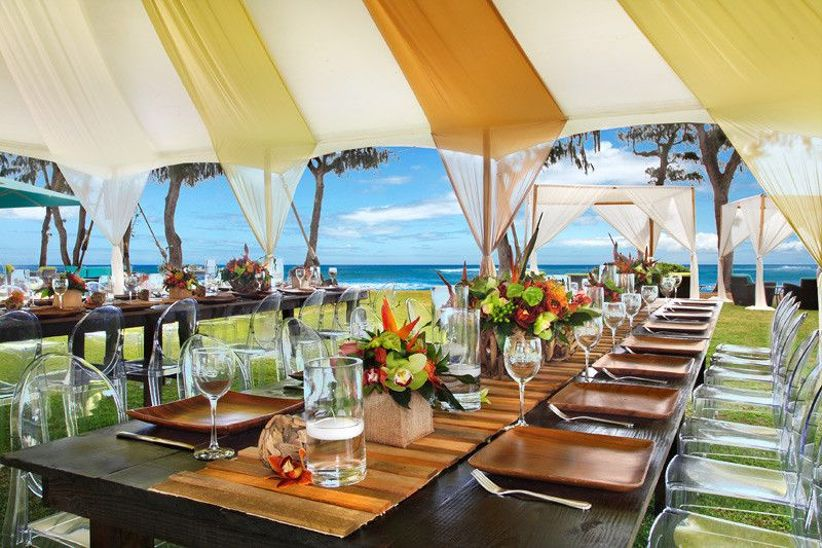 outdoor kauai wedding reception long tables lined with colorful tropical centerpieces beneath yellow and white canopy tent