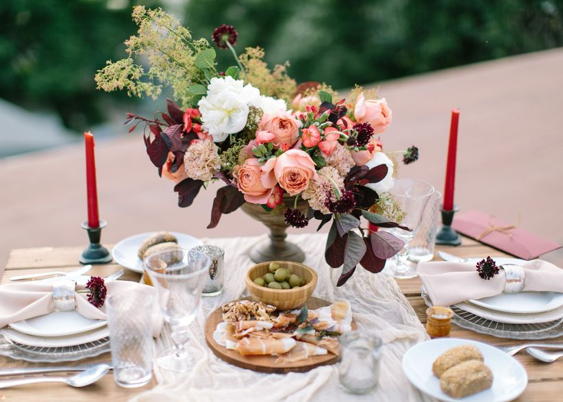 tablescape showing winter wedding colors with red taper candles, bowls of green grapes, white, dishes, and dark burgundy flowers