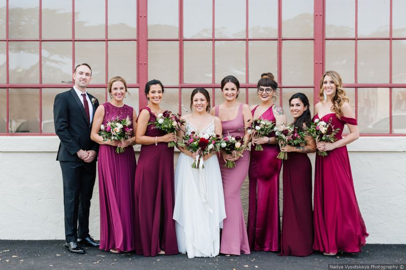 bride stands with bridesmaids wearing dresses in various winter wedding colors—fuchsia, burgundy, and purple
