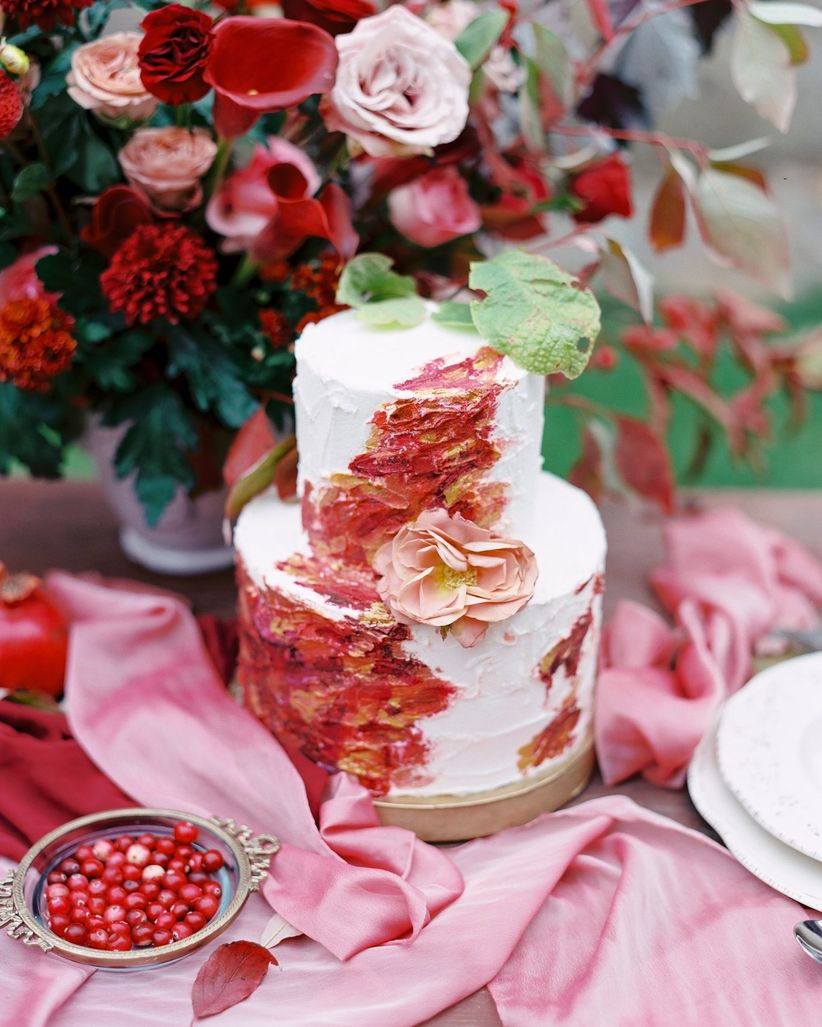 textured buttercream wedding cake decorated with abstract streaks of red, pink, and other winter wedding colors