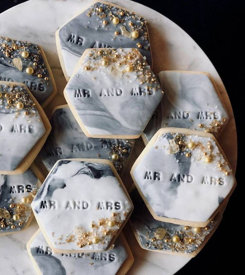closeup of hexagonal-shaped cookies with swirled gray and white frosting and