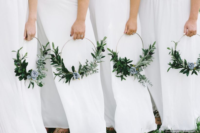 bridesmaids wearing white dresses carrying wreaths