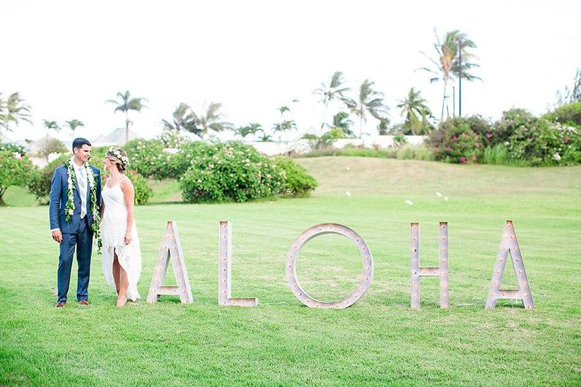 bride and groom smiling while standing next to large marquee letters that spell