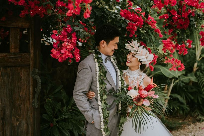 Hawaiian bride and groom wearing leis and smiling at each other