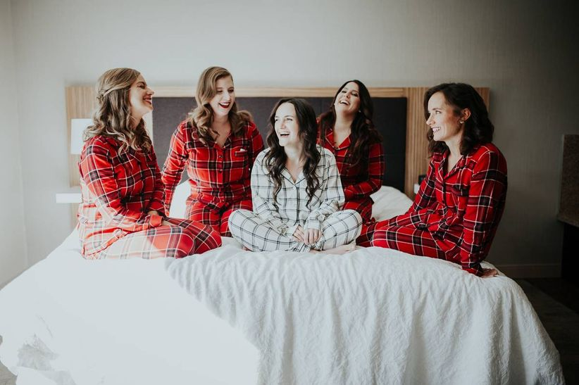 bride and bridesmaids wearing matching red and white plaid pajamas