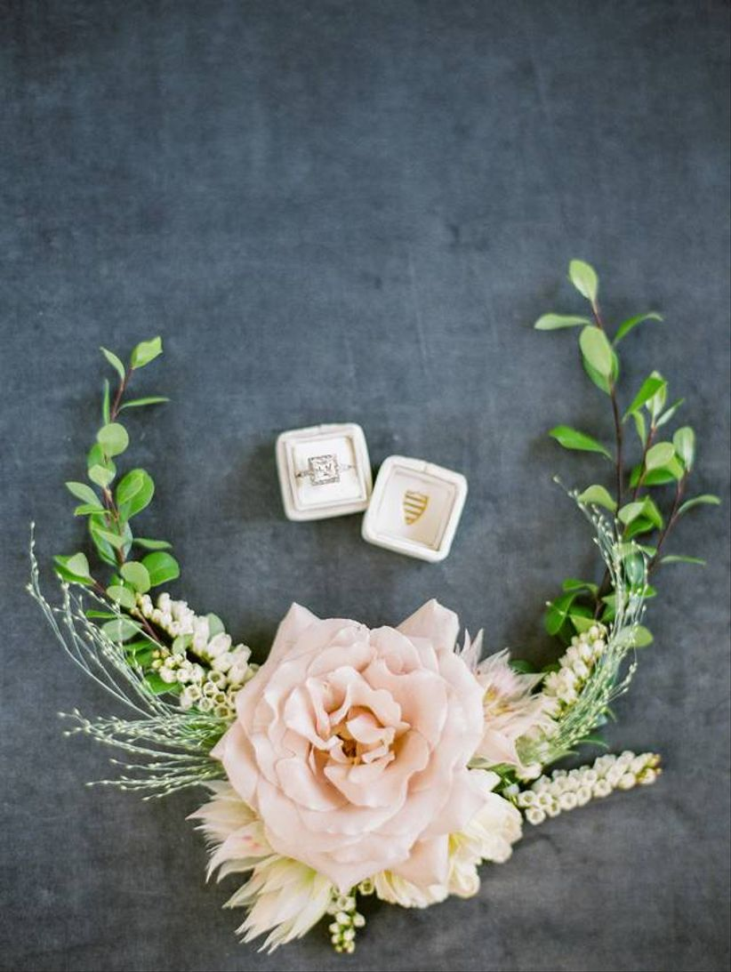 wedding flat lay with blush mrs. box surrounded by flowers and greenery