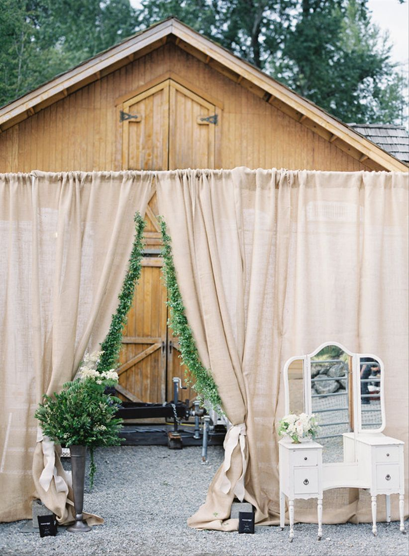 barn wedding venue entrance decorated with blush pink draped fabric and greenery garlands
