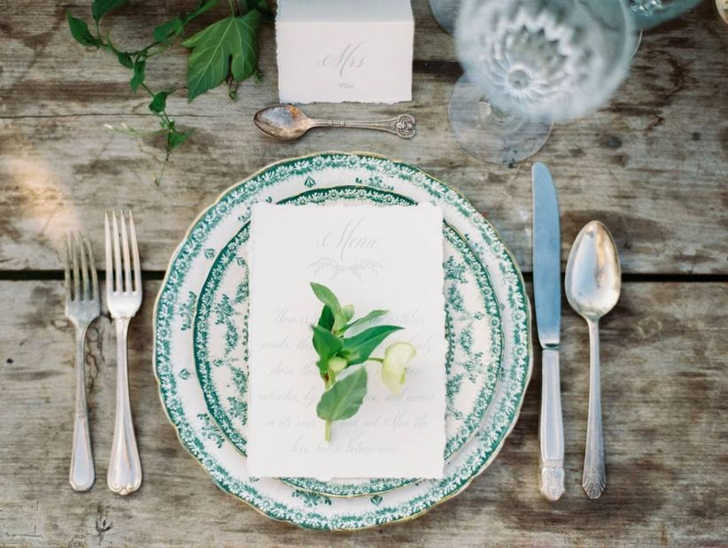 vintage wedding theme place setting with green floral print china and antique silverware