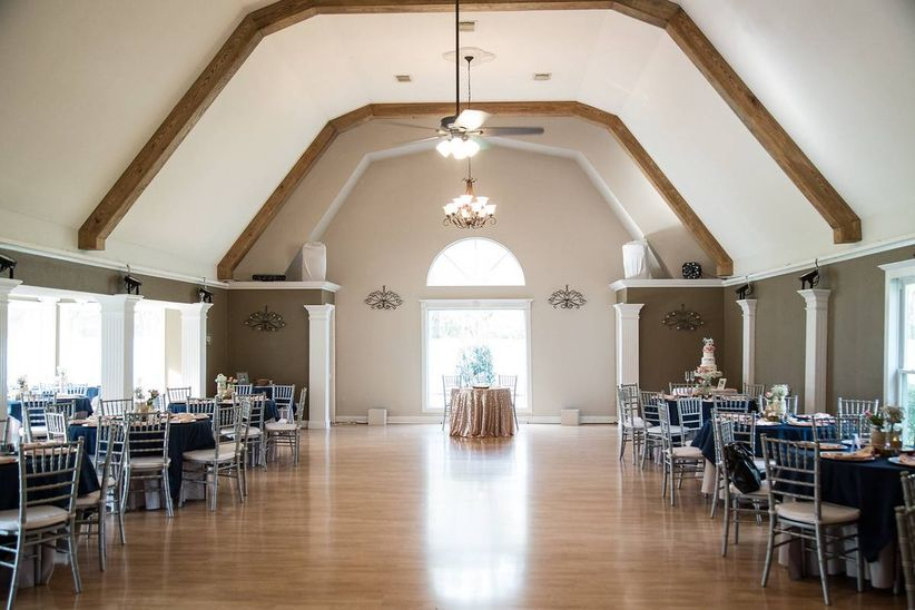 rustic banquet hall with cathedral ceilings and round dining tables along both sides of the room