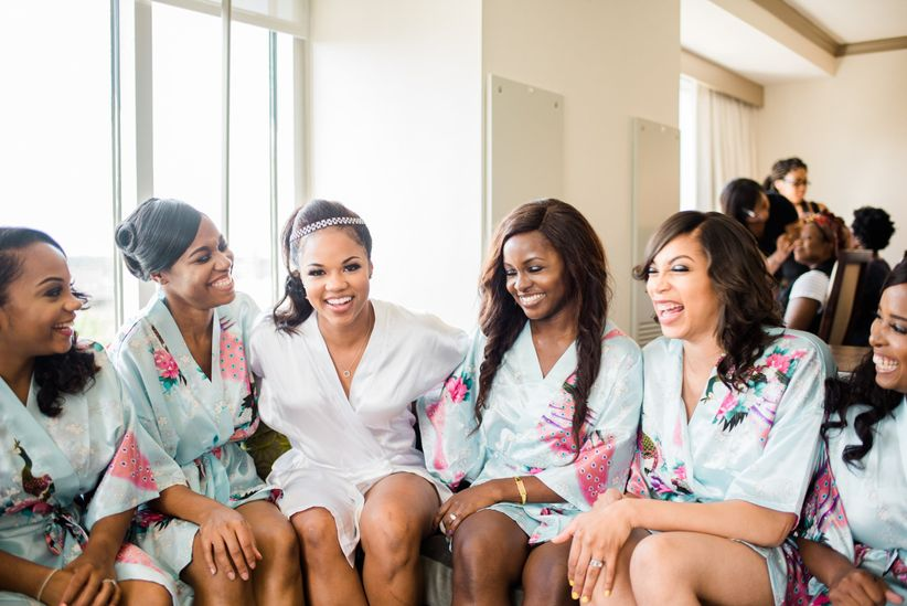 bride and bridesmaids wearing floral robes laughing