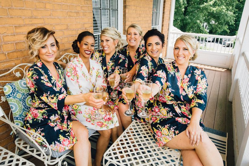 bride and bridesmaids wearing floral robes toasting champagne