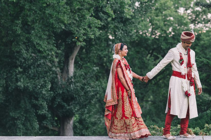 indian wedding couple walking hand in hand