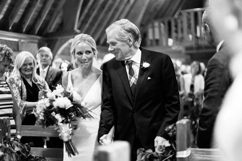 novia y padre caminando por el pasillo en blanco y negro