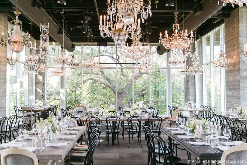 sunlit wedding reception room with floor-to-ceiling windows and assorted chandeliers hanging from ceiling