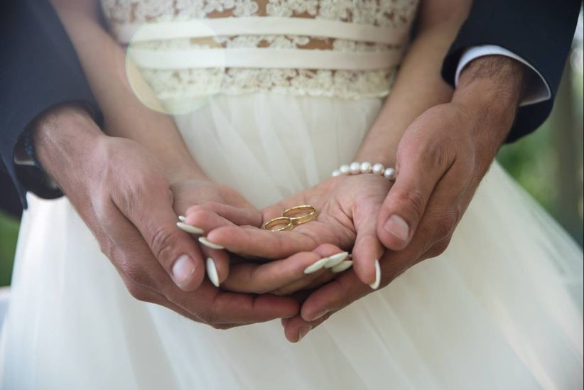 couple holding wedding rings