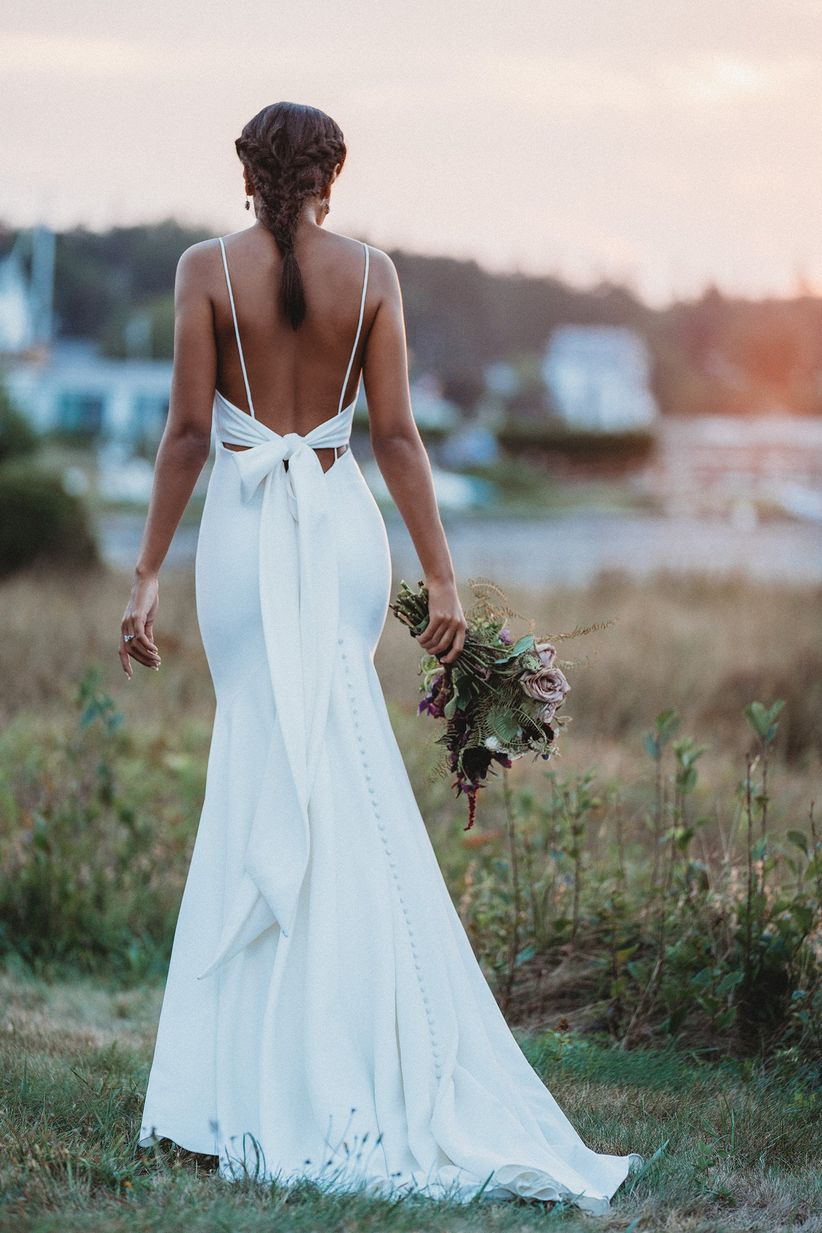 bride walks away from camera wearing crepe fit and flare wedding dress with statement bow