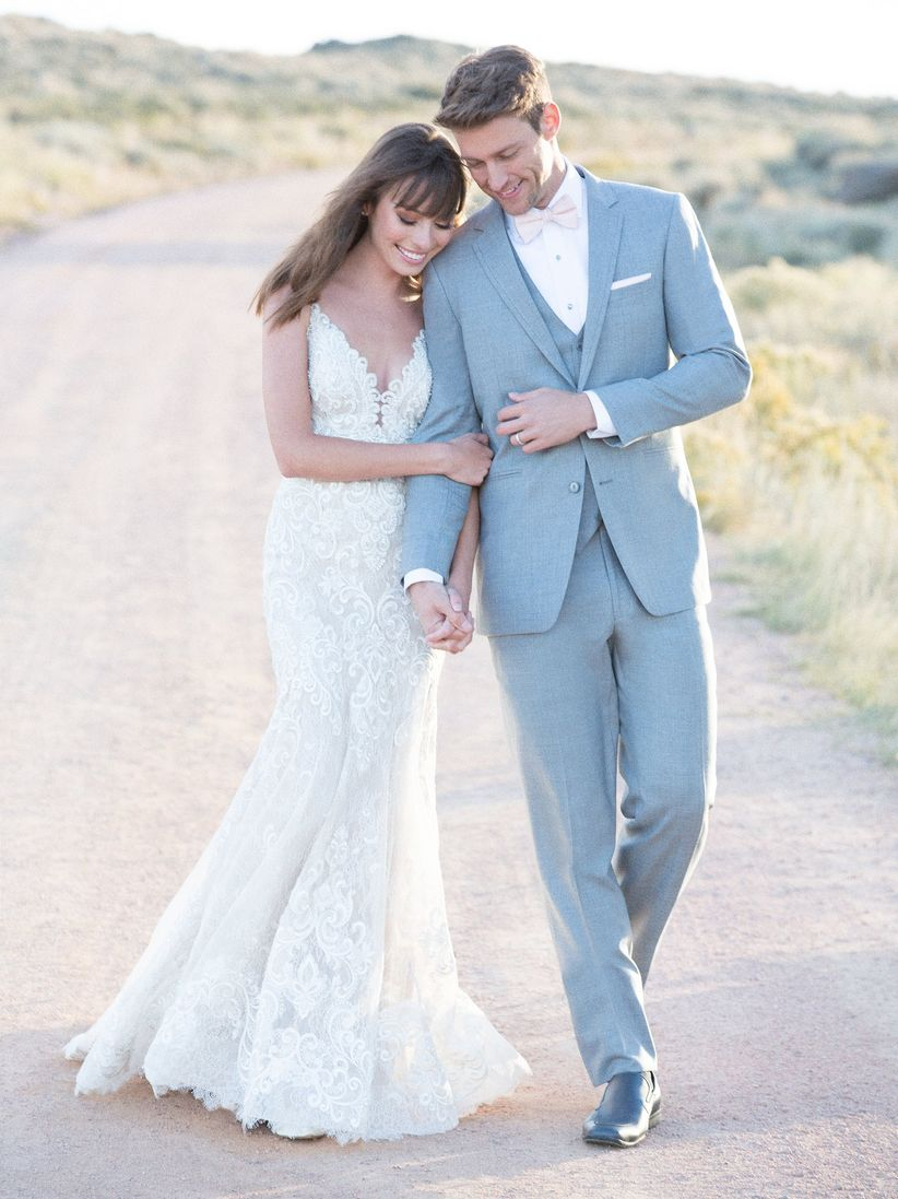 bride and groom hold hands and smile while walking outside at sunset