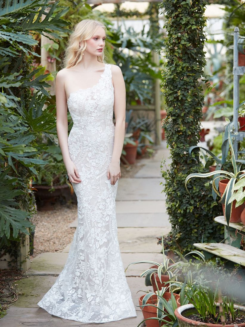 blonde bride poses in a garden wearing a lace one-shoulder wedding dress
