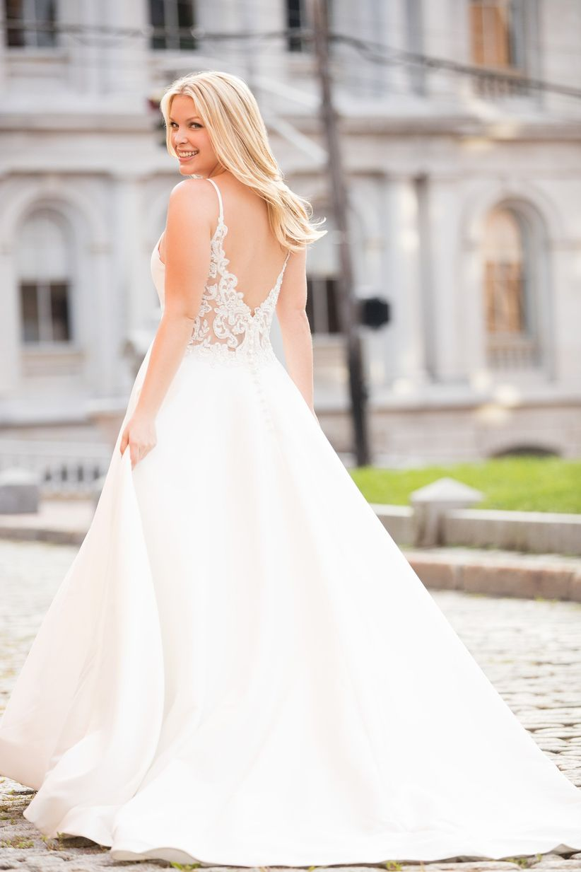 blonde bride wears modern A-line wedding dress with lace illusion back and spaghetti straps