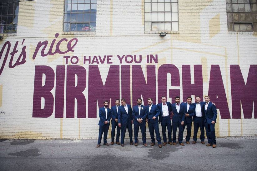 "groom and groomsmen standing in front of mural ""it's nice to have you in birmingham"""